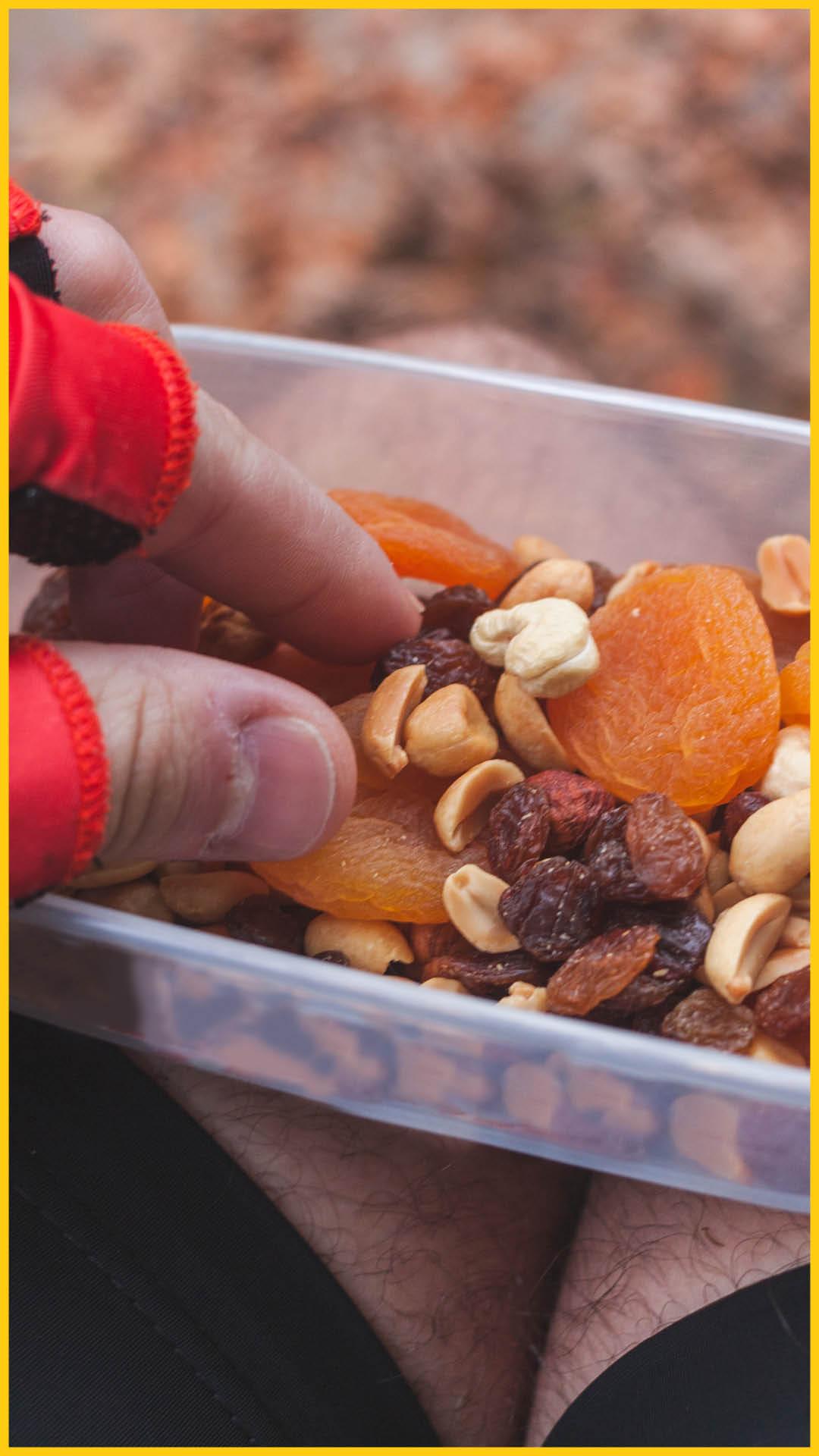 Hand eines Bikers greift in eine Schale mit Studentenfuttrt und getrockneten Früchten