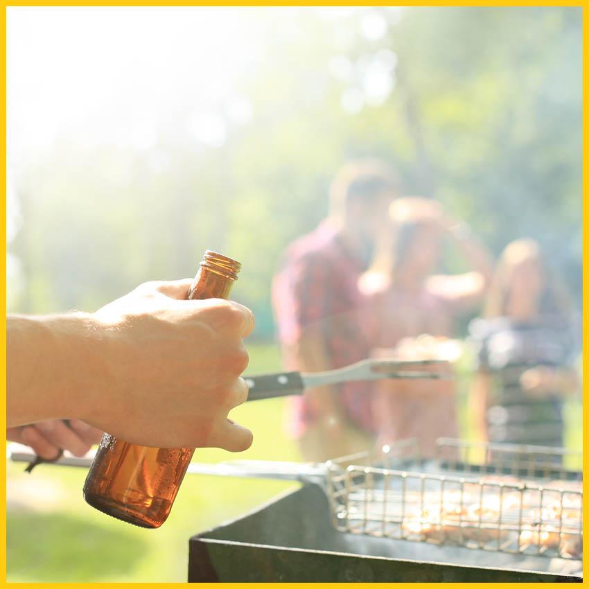 Person an einem Grill hält eine Bierflasche und Grillzange, im Hintergrund eine Personengruppe unscharf