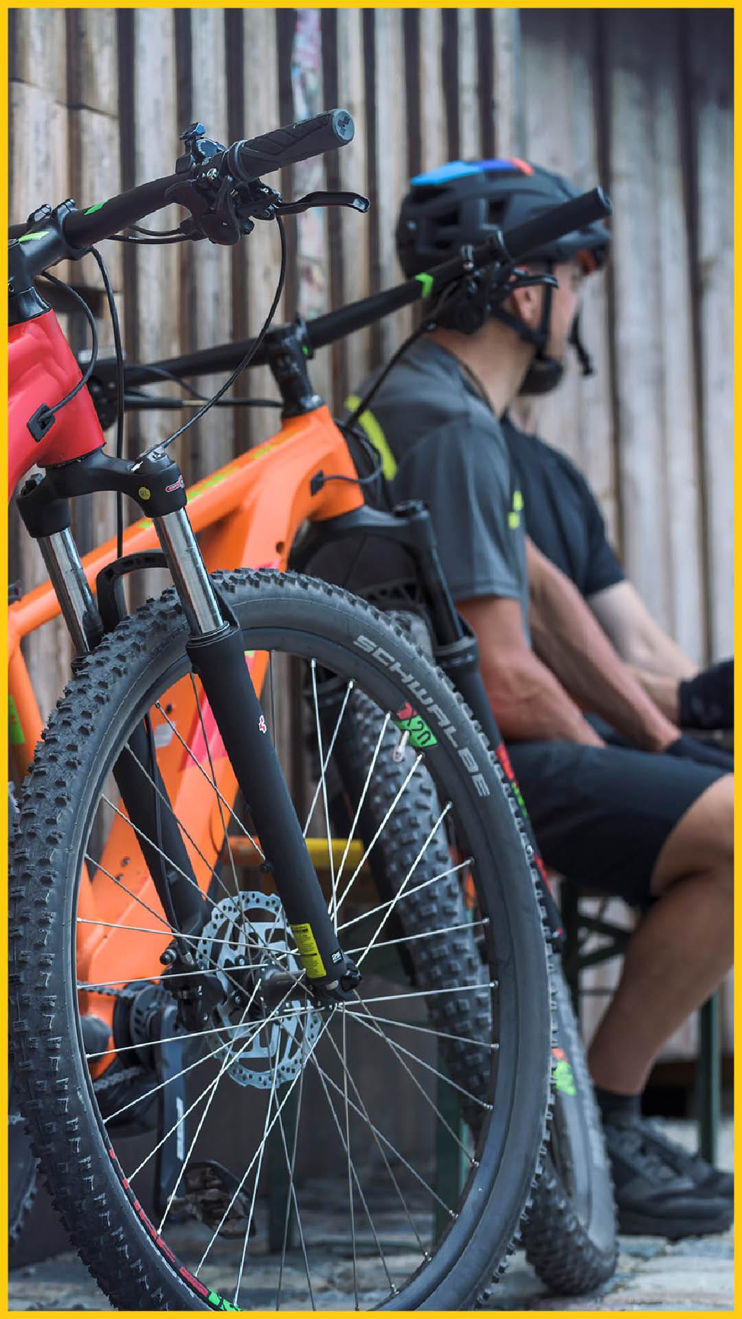 Zwei Männer sitzen neben ihren CUBE Bikes nach einer Radtour