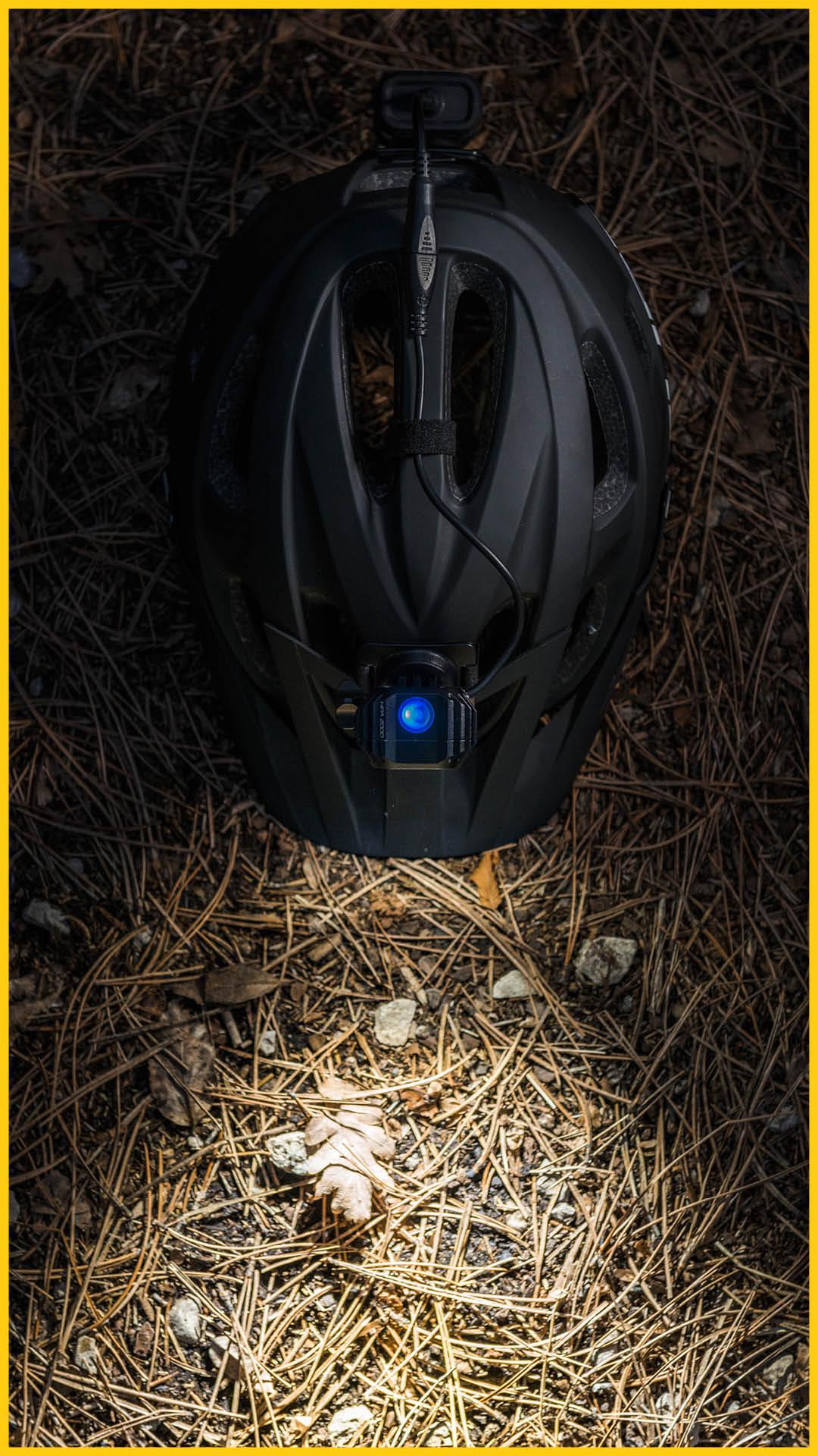 Ein schwarzes Fahrradhelm von CUBE auf vertrocknetem Gras mit blauem Licht auf dem Rennsteig Radweg durchgeführt von Werra Bikes