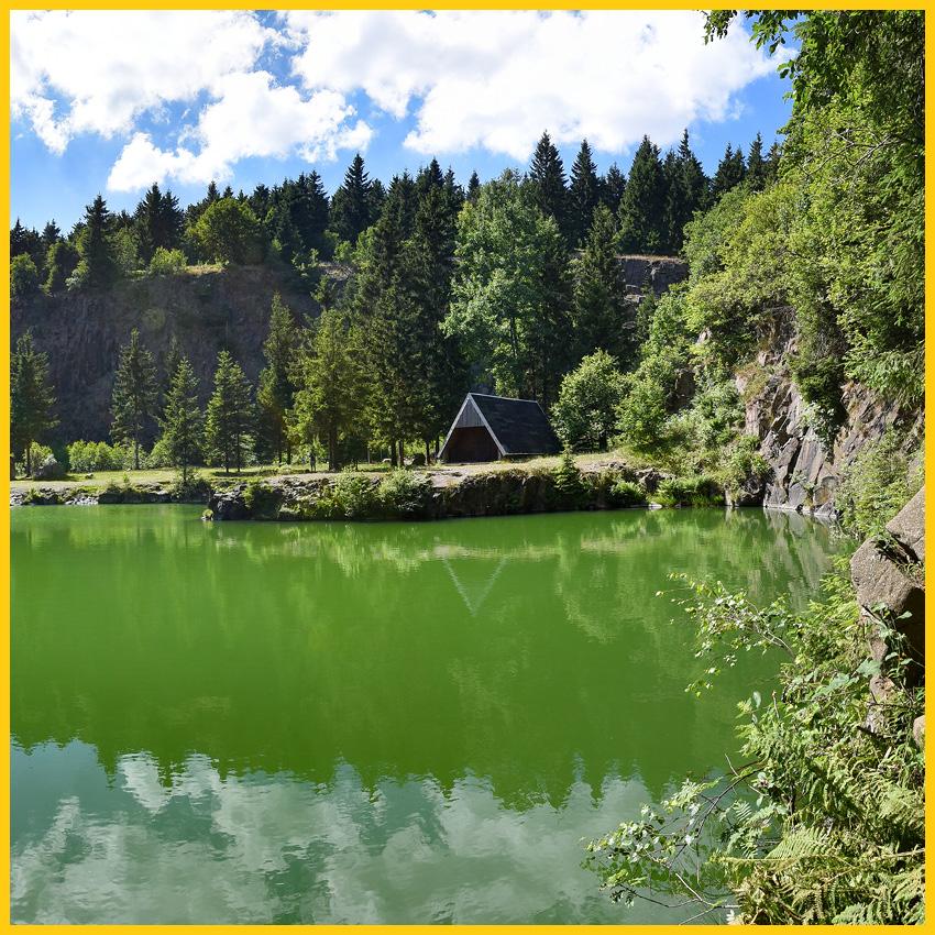 Bergsee Ebertswiese im Thüringer Wald mit grünem Wasser und blauem Hiimmel auf dem Rennsteig Radweg durchgeführt von Werra Bikes