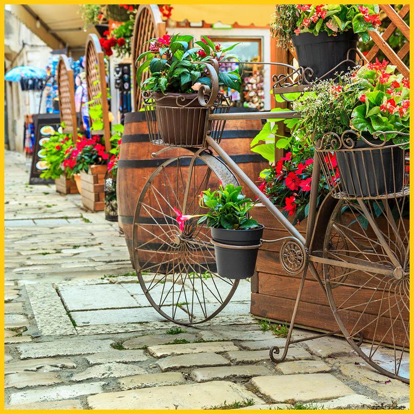 Altes Fahrrad aus Metall als Deko mit Blumentöpfen auf einer gepflasterten Straße in Altenburg auf dem Radweg Thüringer Städtekette durchgeführt vom Werra Bikes