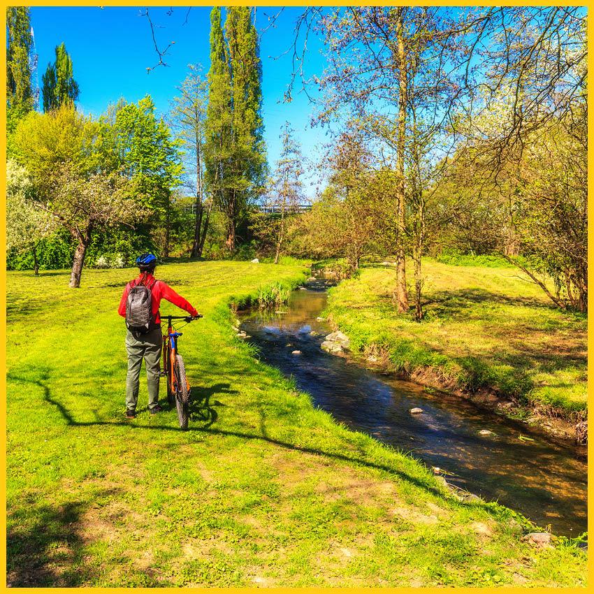 Biker mit Rucksack und Fahhradhelm steht mit seinem Fahrrad auf einer Wiese mit einem kleinen Bach mit Bäumen entlang dem Werratal Radweg durchgeführt vom Werra Bikes