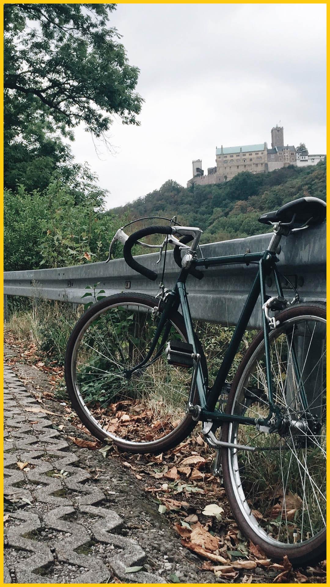 Blick auf die Wartburg in Eisenach, im Vordergrund ein älteres Rennrad an der Leitplanke angelehnt auf dem Werratal Radweg durchgeführt vom Werra Bikes
