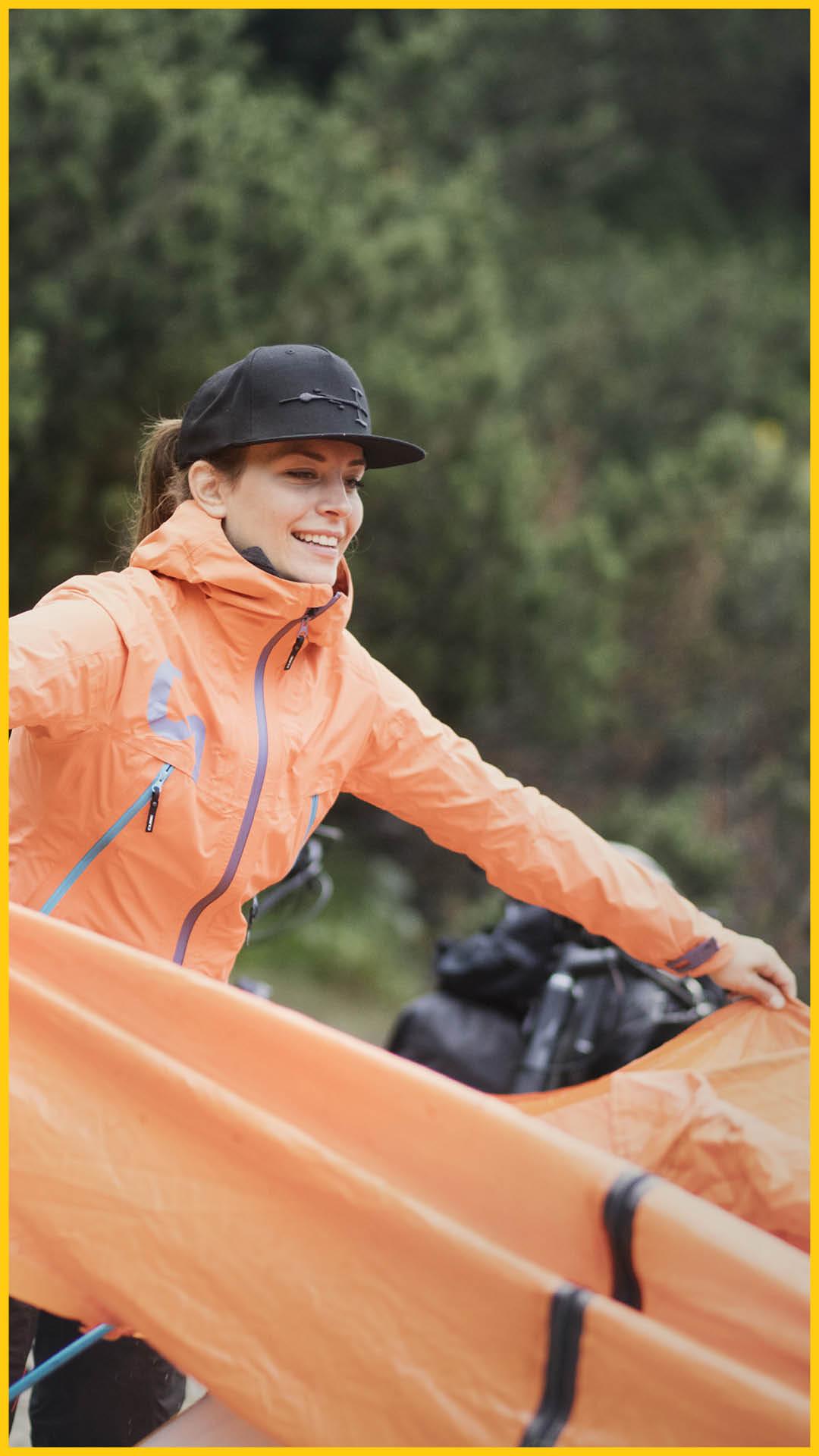 Frau mit CUBE Regenjacke hat die Außenhaut eines Zeltes in der Hand auf dem Werratal Radweg